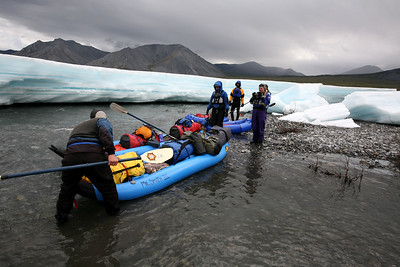 KONGAKUT RIVER, AK - Bobby pulls his inflateable kayak (ducky) from the pebble bar after the group stops amongst the ice to stand, stretch and jump around some to warm up.