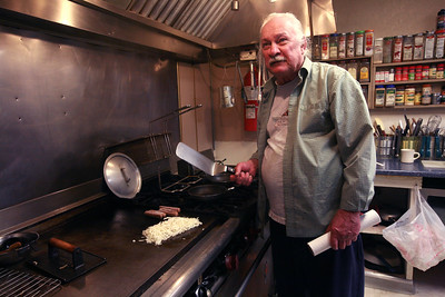 KAKTOVIK, AK - Camp X; The legendary Walt Audi at his usual station frying up hashbrowns. Walt is a long time Alaska bush pilot (now retired) who runs the Waldo Arms Hotel in Kaktovik.