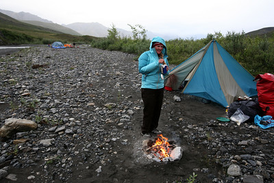 KONGAKUT RIVER, AK - Camp II: North Bend; Jessie warms up with a hot drink by the fire.