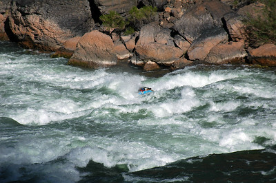 """GRAND CANYON, AZ - From our scouting vantage point, we watch Larry battle his way through the torrent that is Lava Falls Rapid (Mile 179) along river left where the infamous """"Cheese Grater"""" has been known to tear rafts to ribbons in seconds."""