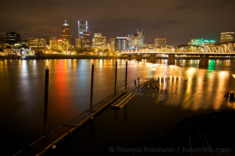 Two people stand near the end of a dock watching the Portland skyline reflect off the Willamette River in Portland, Oregon.