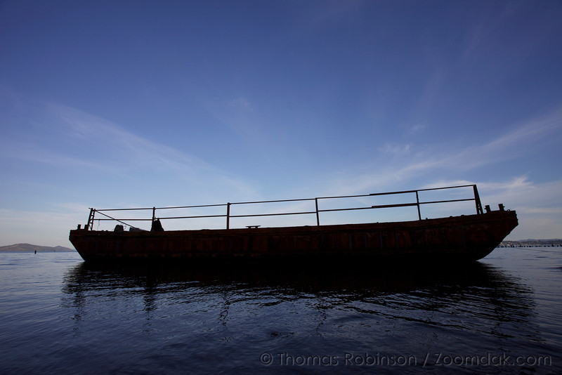 An abandoned rusted boat anchored on the edge of the Columbia River near Astoria, Oregon.