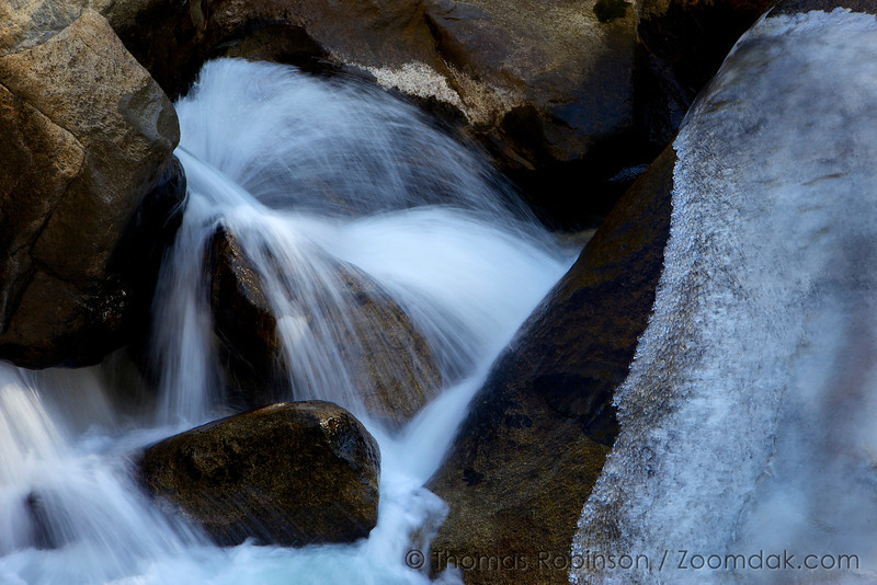 The Merced River shoots through a funnel in the rocks creating an epic water explosion on a winter day in Yosemite National Park.
