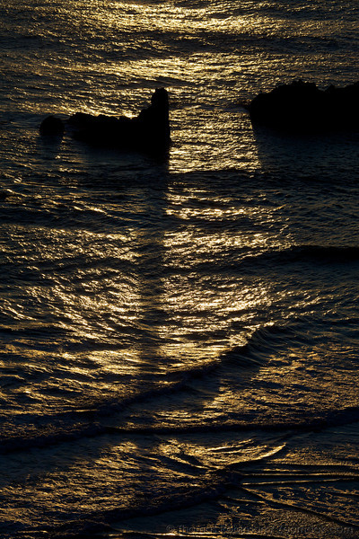 The long shadows of rocks stretch across the waves during sunset at Ecola Point on the Oregon Coast.