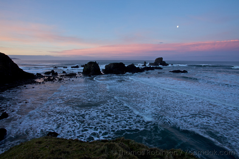 The moon shines over the rocks below Ecola Point during sunrise.