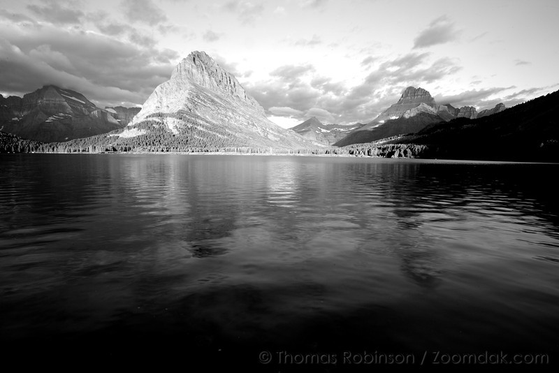 Grinnell Point ignites with the morning sunlight across Swiftcurrent Lake in Many Glacier.