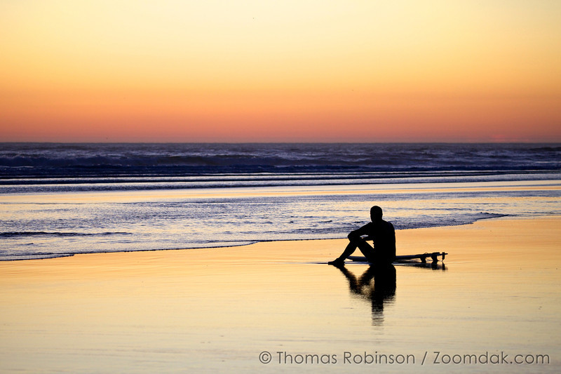 A surfer reflects about the beautiful beach evening unfolding before him.