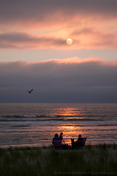 A couple sits upon the dunes enjoying the sunset ambiance in Cannon Beach, Oregon.