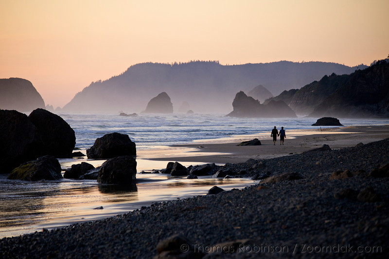 A couple walks hand in hand down the beach at sunset at Arcadia Beach on the Oregon Coast.