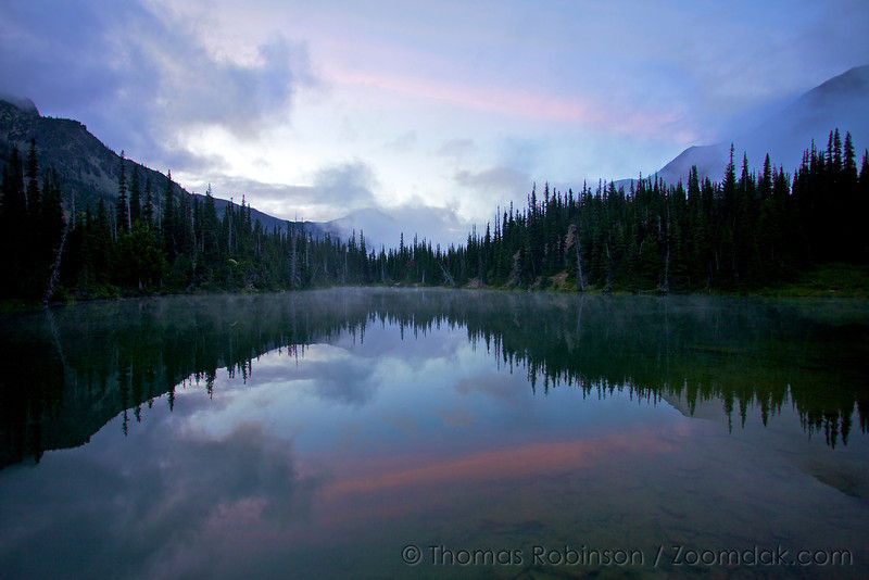 Sunset color glows above Royal Lake with clouds partly obscuring Grey Wolf Peak.