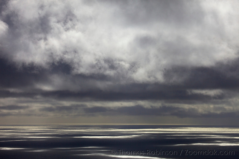Patches of light glimmer on the Pacific Ocean as dramatic clouds roll above.