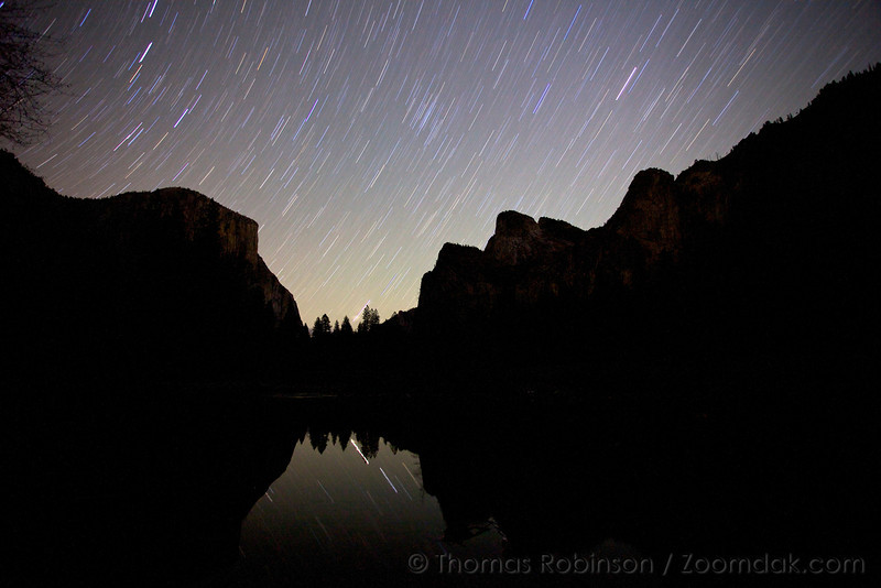 Star trails illuminate El Capitan and Cathedral Peaks reflected off the dark waters of the Merced River in Yosemite Valley.