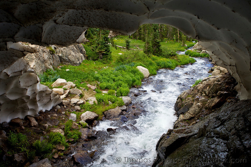 Ouzel Creek flows under the gate to this large snow cave along the Bluebird Lake Trail in the Wild Basin area of Rocky Mountain National Park.