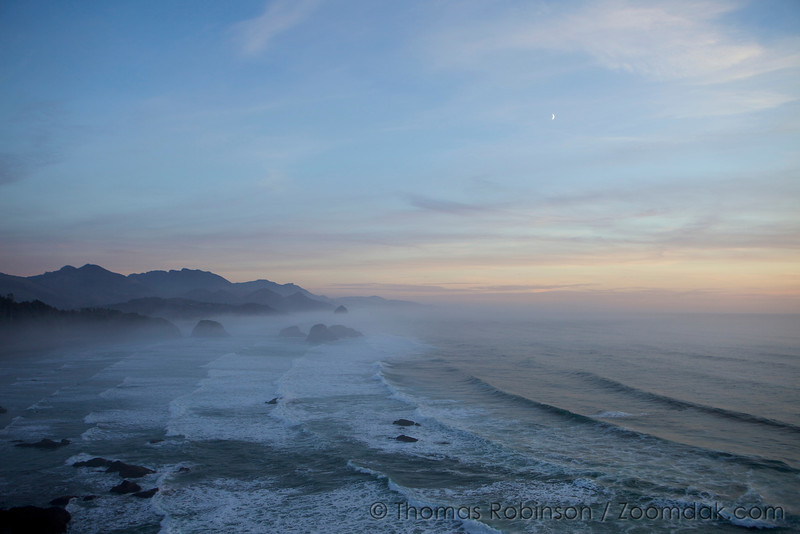 The crescent moon glimmers above the fog settled along the Pacific Ocean at Ecola State Park near Cannon Beach, Oregon.