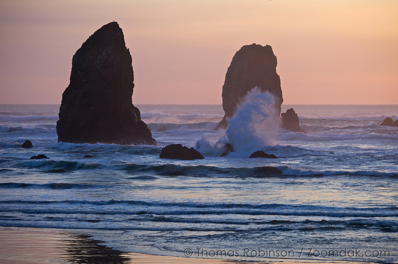 Waves splash against rocks in front of the Needles at sunset.