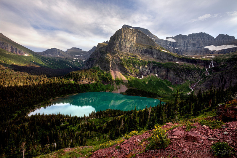 The view from the trail to Grinnell Glacier shows the epic landscape of Glacier National Park with the milky blue color of Grinnell Lake, the rocky buttes of Angel Wing and Mount Gould, and steep dropoff of the trail.