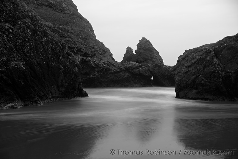 Waves wash around the seastacks of Cape Sebastian State Park with a keyhole through the rocks creating an amazing black and white seascape. On the Oregon Coast Highways near Gold Beach.