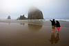 Two friends point and gaze across to Haystack Rock in clouds in Cannon Beach, Oregon.