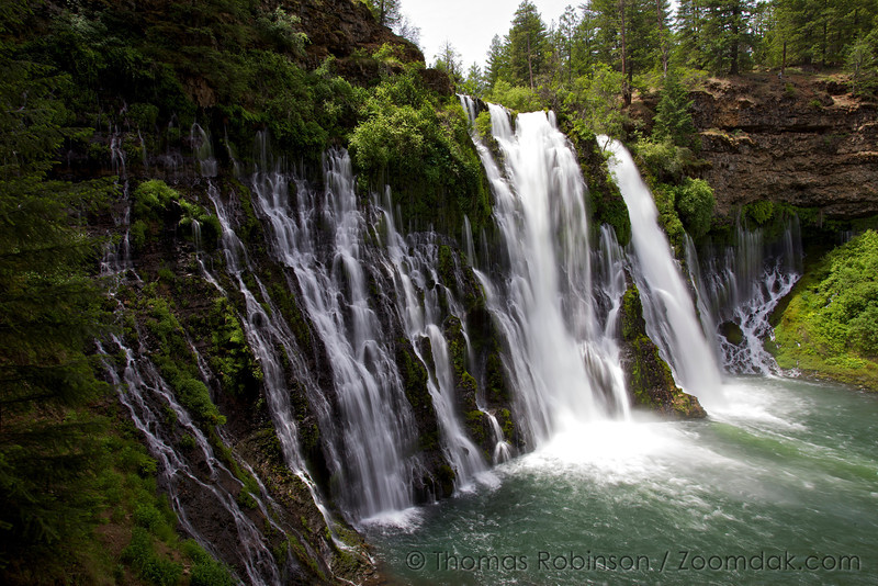 """The waterfall of Burney Falls not only comes from the above ground Burney Creek but also through the earth via underground springs. The water falls from a height of 129 feet (39 meters) into a 22 foot (6.7 meter) deep pool. 100 million gallons of water flow over Burney Falls daily, even in late summer.<br /> <br /> The falls were called """"the Eighth Wonder of the World"""" by President Theodore Roosevelt, and were declared a National Natural Landmark in December 1984."""