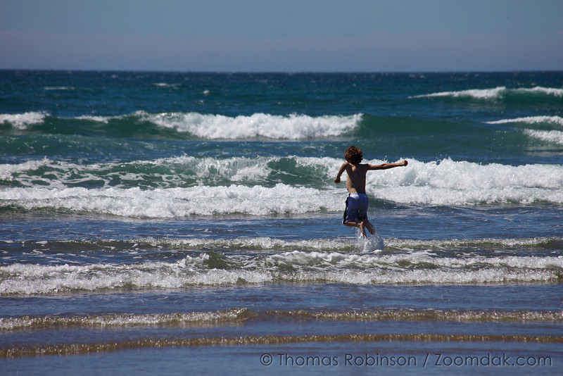 A kid enjoys like jumping in the waves of the Pacific Ocean,
