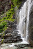 A waterfall from the glaciers below Mount Grinnell sprays over the trail to Grinnell Glacier.