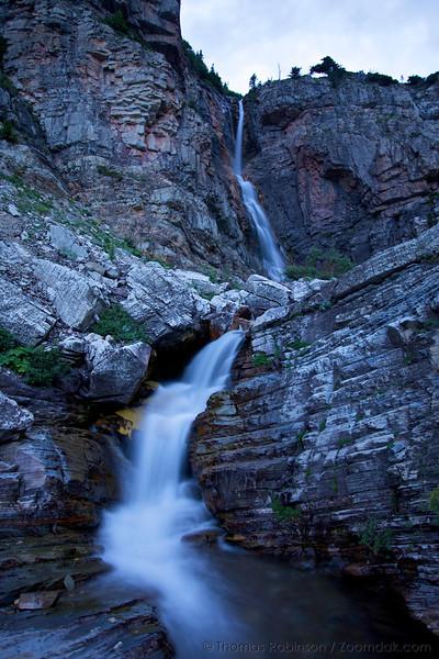 Apikuni Creek falls down Apikuni Falls in Glacier National Park.