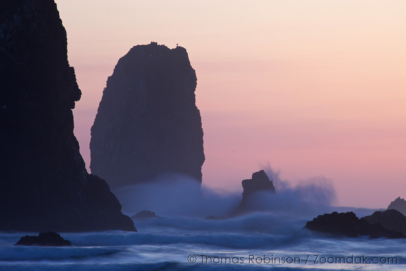A slow exposure shows the motion of a wave against Monk rock near Haystack Rock.
