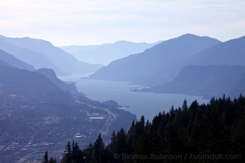 The view from the top of Coyote Wall looks down the Columbia River Gorge with Hood River and I84 far below. Dog Mountain in the tallest mountain visible on the north (left) side.