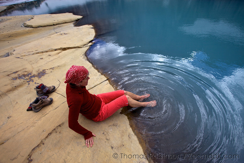 Trina Robinson, clad in red, dips her feet into Upper Grinnell Lake, one of the coldest lakes in the United States.