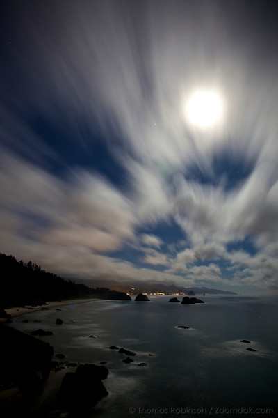 A slow exposure shows the motion of clouds over the Cannon Beach and the Pacific Ocean at night.