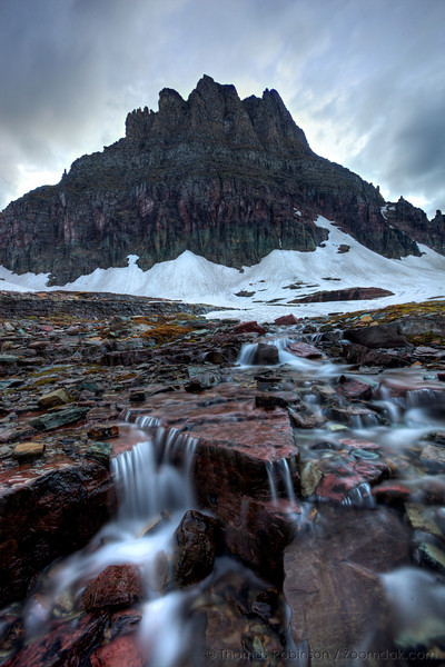 Waterfalls cascade down from the snow melt off below Clements Mountain along the Hidden Lake trail in Glacier National Park, Montana.