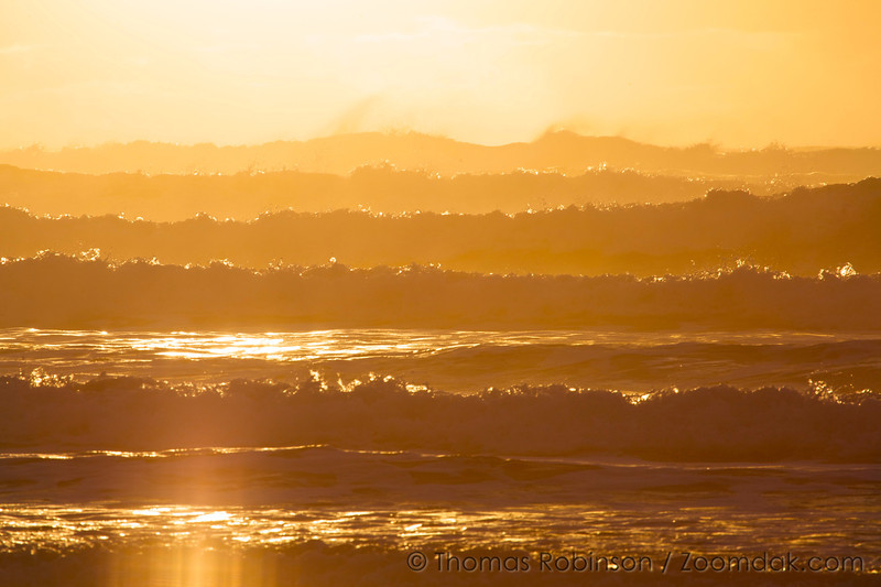 Golden lighting of sunset refracts through a series of waves at Manzanita Beach.