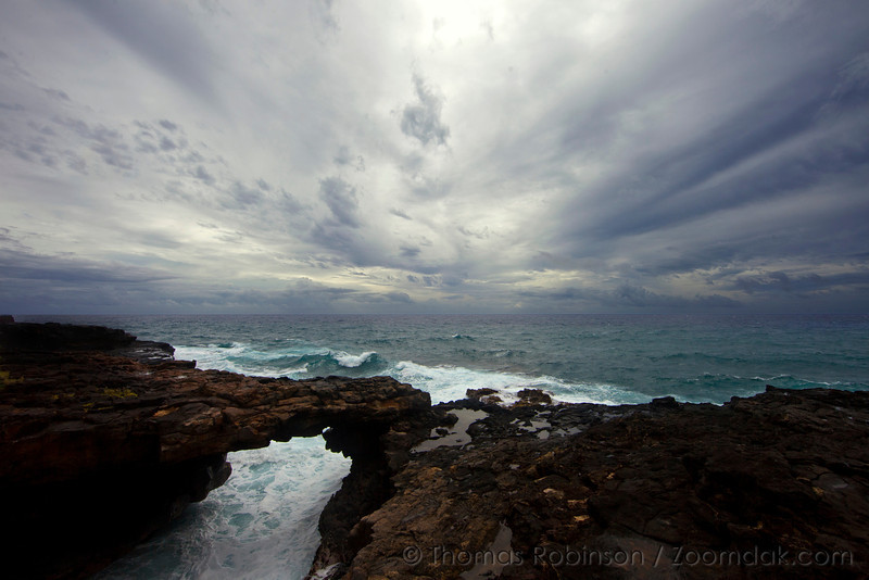 A sea arch stands amongst the waves and weather on the west shore of Kauai near Poipu.