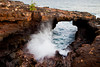 A large wave crashes under a lava arch on the west shore of Kauai near Poipu.