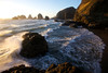 A wave crashes off a rock on the windy beaches of Oceanside, Oregon during sunset.