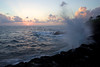 A large Pacific wave crashes up at sunset on the west shore of Kauai in Poipu.