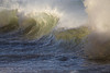 Light shines through the back of waves as they crest to the shore of Oceanside, Oregon.