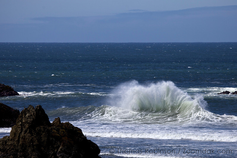 Two waves erupt as a previous wave slides back to sea.