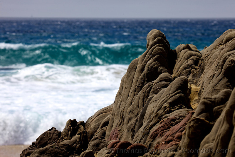 Curving rock formations stand against the ocean at Garrapata State Beach in California.