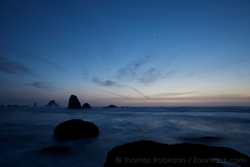 A crescent moon glints above the silhouettes of the rocks along the Oregon Coast near Indian Beach.