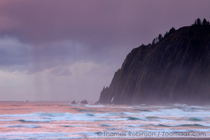 The Neahkanie Arch peeks out as rain clouds gather above the Neahkanie Cliffs at sunset in Manzanita, Oregon.