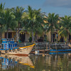 Morning sun on several traditional wooden boats along the Thu Bon River in Hoi An, Vietnam