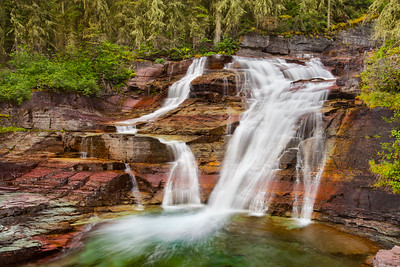 A waterfall cascading over layers of multi-colored rocks in Glacier National Park, Montana