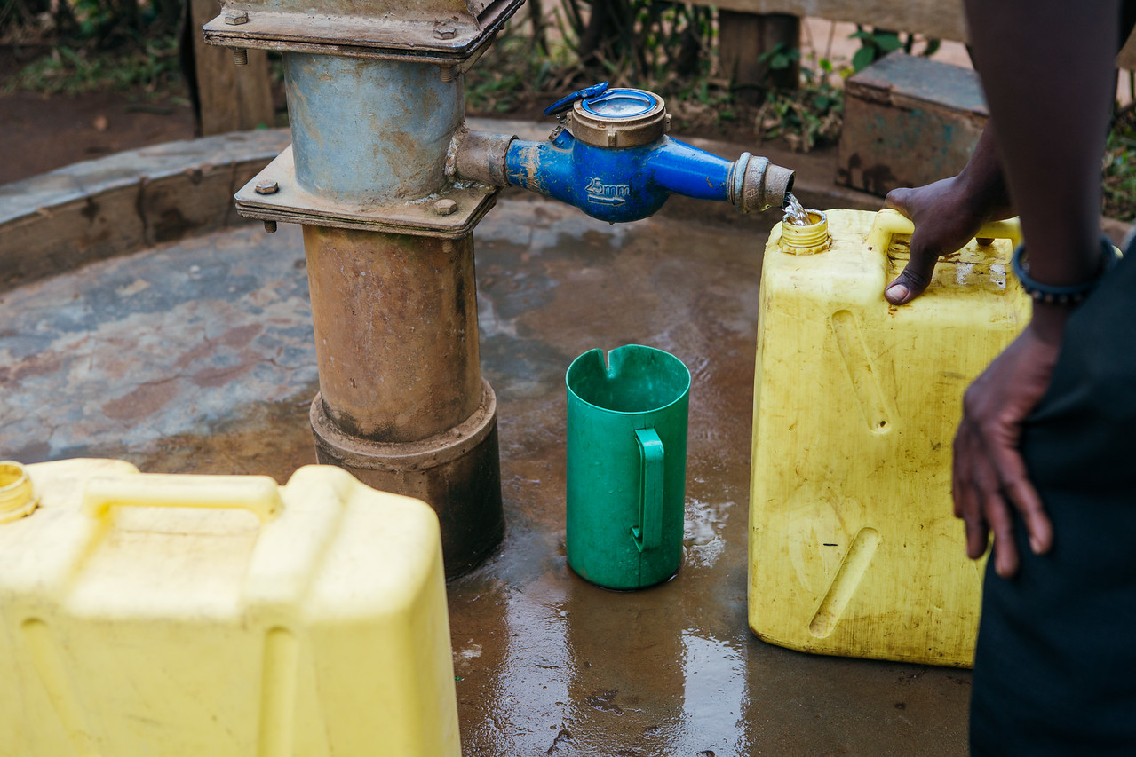 Jerry cans being filled at a water point in Uganda.
