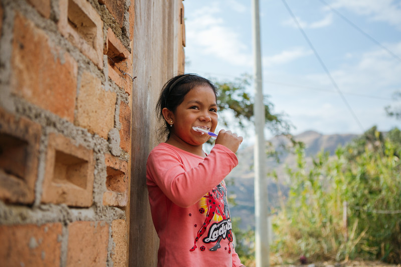 A young girl brushes her teeth using water from a reliable and improved source.