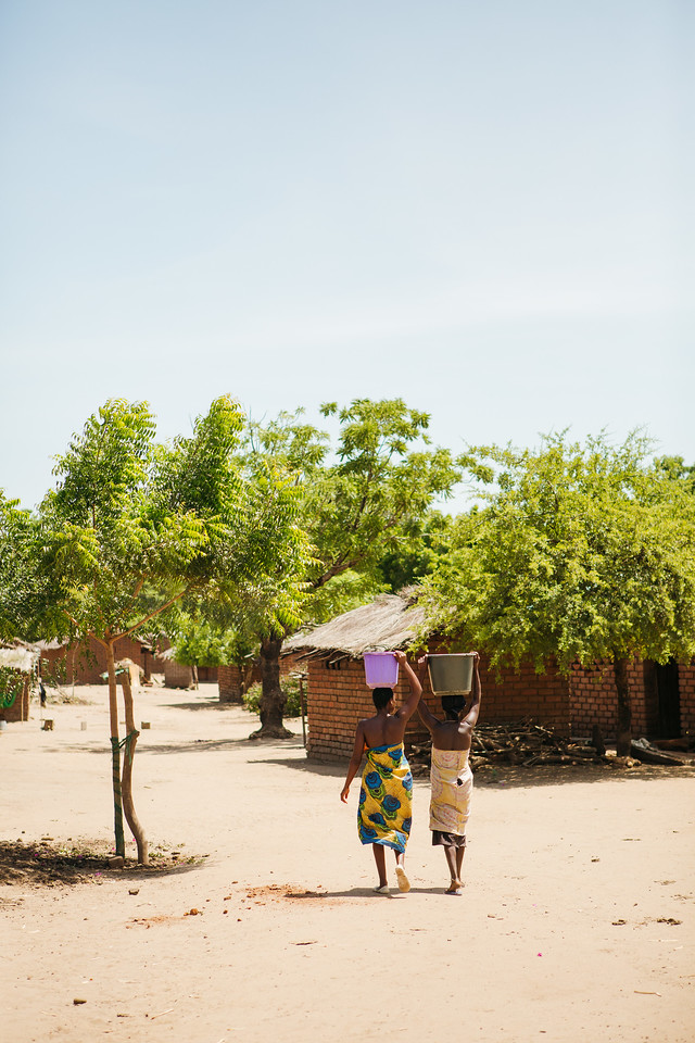 Two women carry full water buckets in their community in Chikwawa, Malawi.