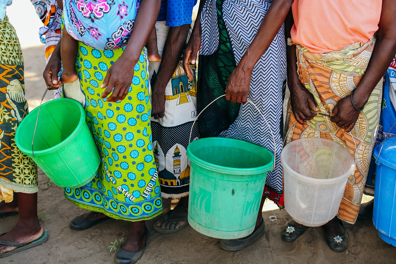 Woman wait to fill their buckets with water at a community water point. Women and girls often spend up to six hours per day collecting water.