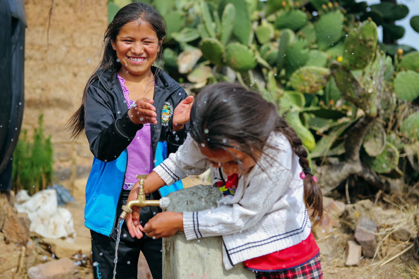 Two girls in rural Bolivia play with water while washing their hands at their newly installed water tap. Read their full story: www.waterforpeople.org/stories/the-town-of-thagoni