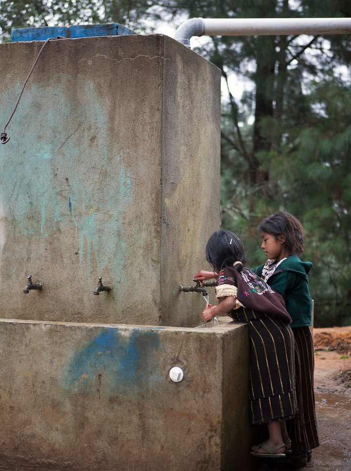 Two girls wash their hands at a water point in Guatemala.