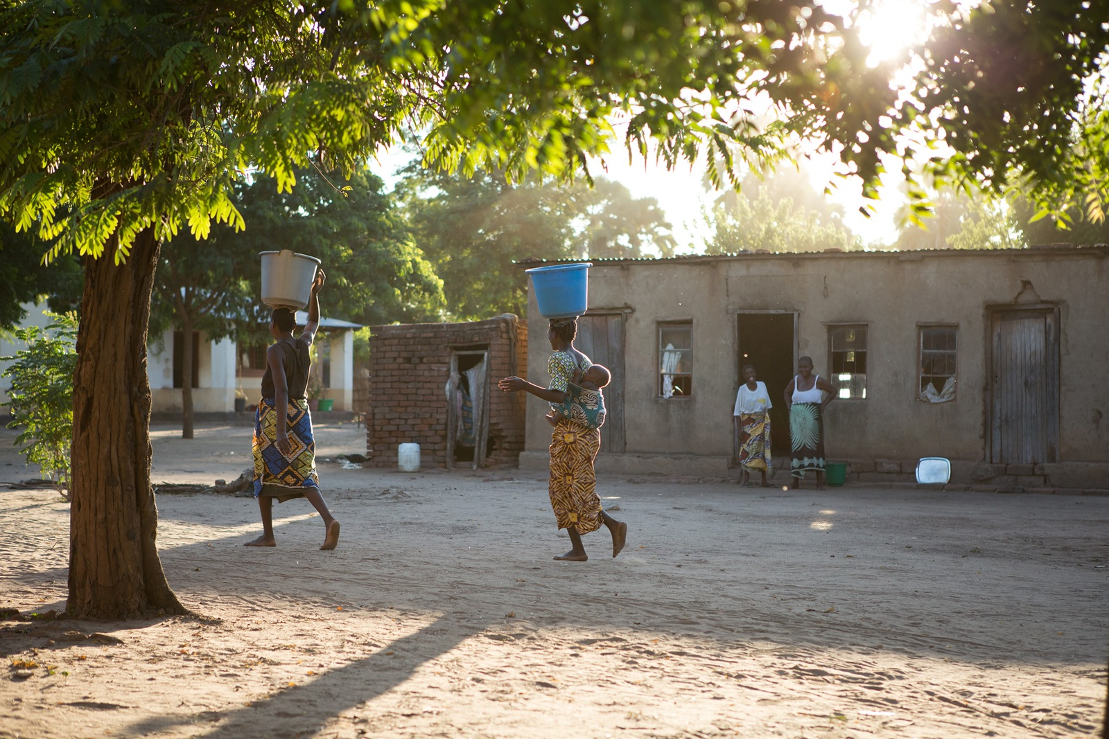 Women walk through their community carrying water buckets. Read more about how women and girls are affected by water access: https://www.waterforpeople.org/stories/girls